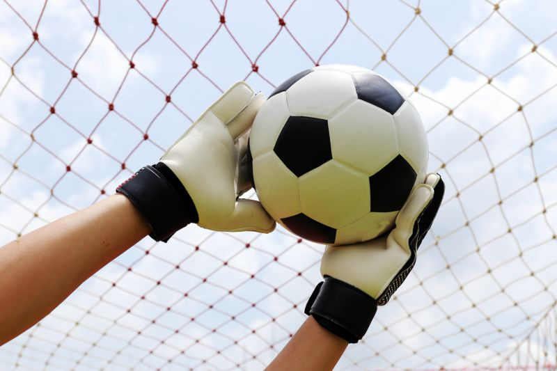 goalkeeper's hands reaching for foot ball © kungverylucky - fotolia.com
