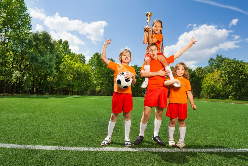 Happy children with golden cup stand in pyramid © Sergey Novikov - fotolia.com